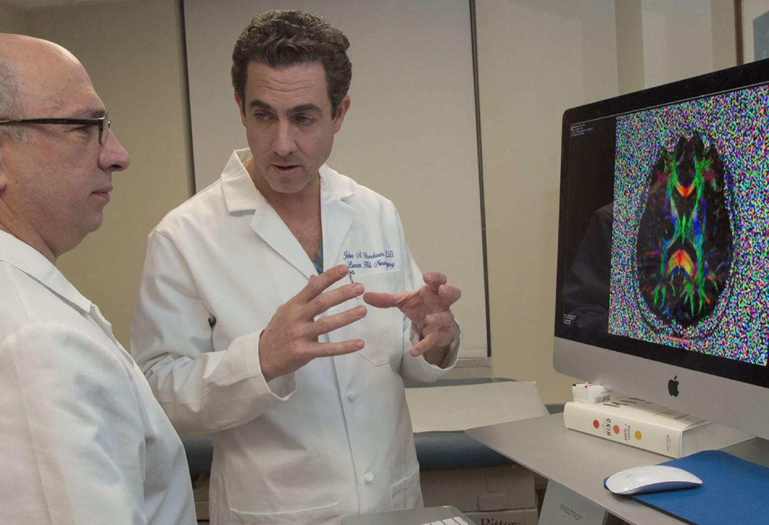 Two doctors in lab coats discuss a brain scan that is showing on a computer monitor.