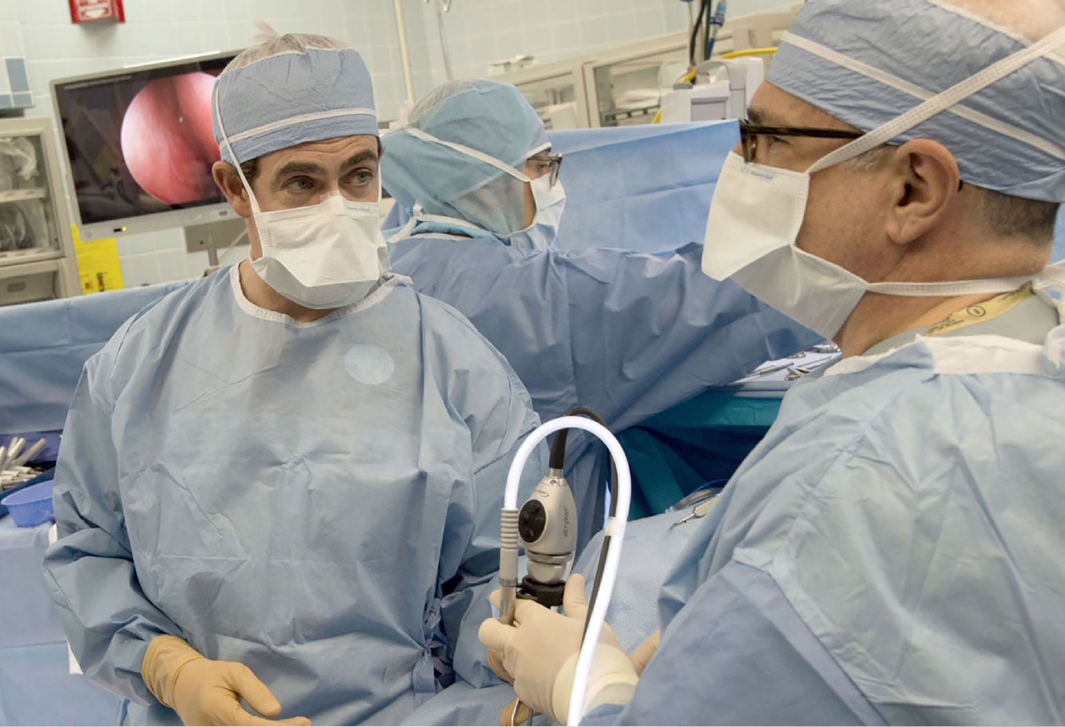 Three surgeons are performing surgery in an operating room