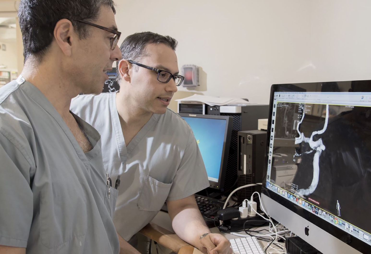 Two male doctors wearing scrubs discuss a scan they are looking at on a monitor