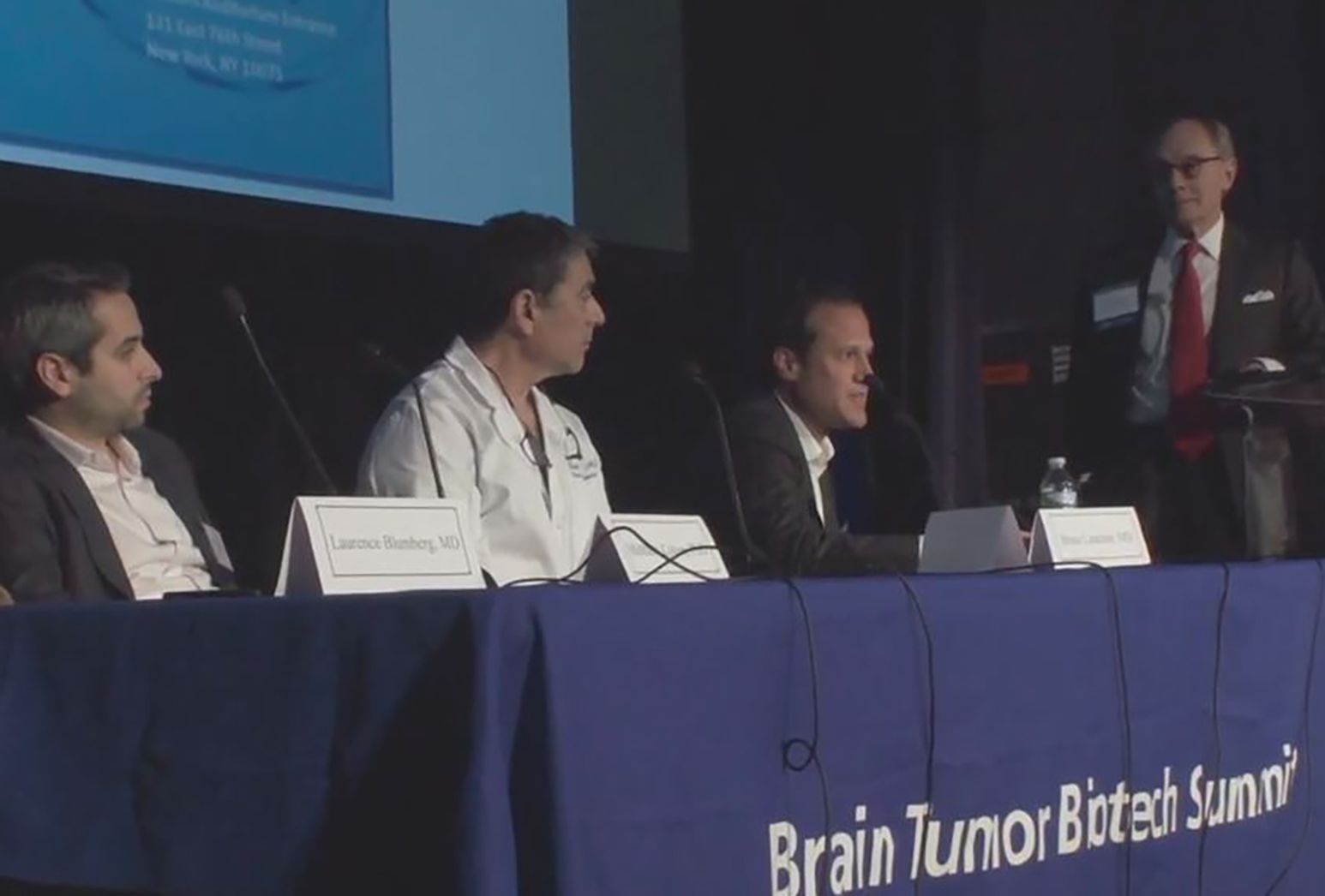 Doctors sitting at a table on stage during a medical conference