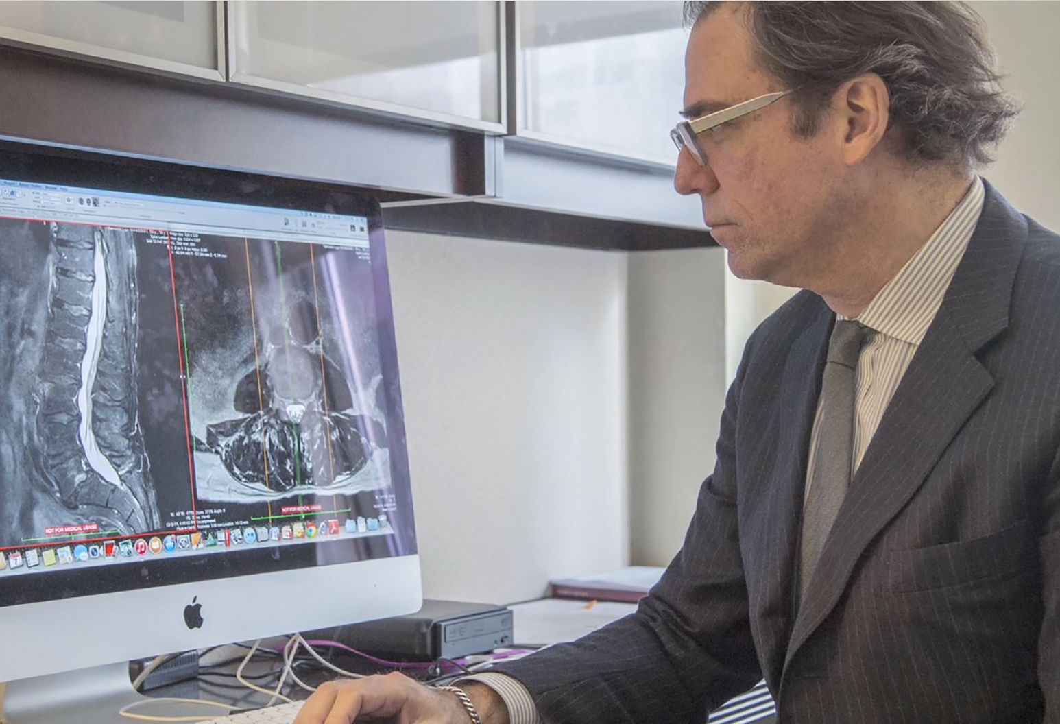 Man wearing a suit is sitting at his desk looking at spine scans on a computer