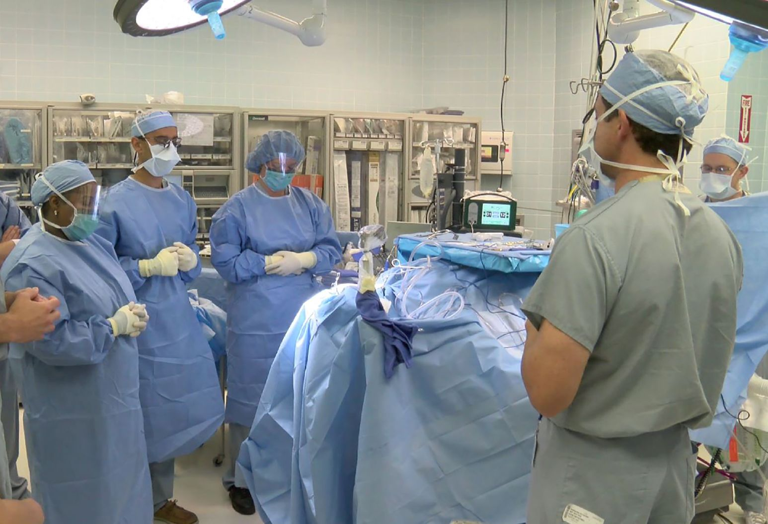 Surgeons and nurses in an operating room take a moment of silence before beginning a procedure